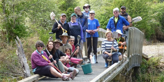 Tarawera Trail planting crew gather on a bridge.