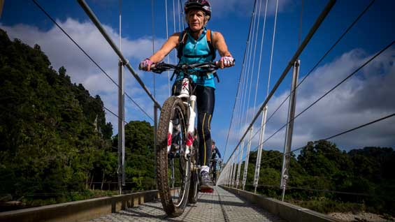 Sharon Renwick riding across the Heaphy Track suspension bridge. Photo: Stephen Roberts.