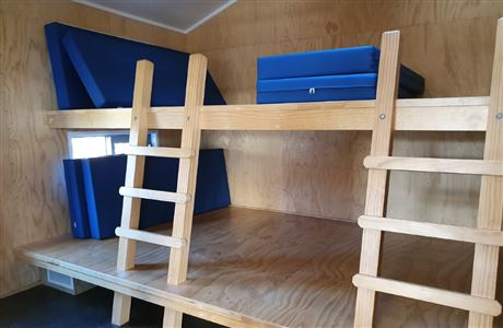 Two bunks with access ladders and mattresses