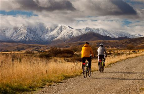 Cyclists and snowy mountains, Otago Central Rail Trail.