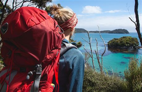 Woman looking out to clear waters from Rakiura Track.